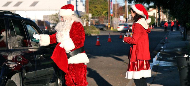 Santa Giving OUt Gifts - Carlsbad Christmas Bureau